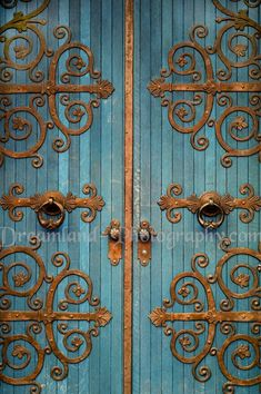 Turquoise wood door with brass scrollwork. Gorgeous