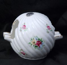 Enesco of Japan ashtray in the shape of a ball, there are two clover shaped cutouts on either side with places to place the cigarette. It is trimmed in gold. Is white porcelain with yellow, blue...