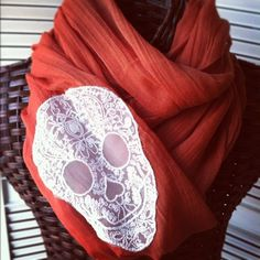 """This """"Preppy Pirate"""" scarf is a great addition to any outfit. 100% viscose measuring 35"""" by 68"""".  Color: Terra Cotta with white skull applique"""