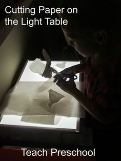Cutting Paper on the light table by Teach Preschool