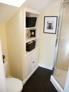Angled walls are a great opportunity for built-in storage. In this small attic bathroom, the shelving unit is built right into the slant of the roofline.