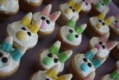 Easter Bunny Mini Cupcakes frosted decorated with pastel candy corns for ears, mini chocolate chips for eyes, and easter m/m for noses.