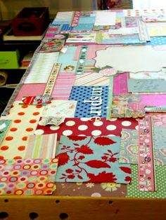 desk covered with scrap fabric and paper, top with glass.  Do this with our white dining table when the top gets destroyed!!
