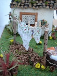 Fairy house with clothesline and tiny clothes!  Love the pine cone shingles on the roof!