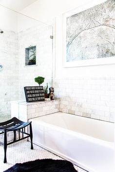 White bathroom with marble tile and a vintage stool.