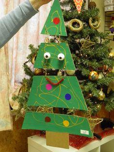 grote kartonnen driehoek versneden, beschilderd en aan elkaar gehecht met touwtjes. Daarop met glinsterverf een slinger getekend en versierd met kleeffiguren