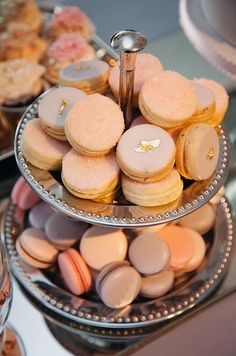 Pastel colored macarons are topped with pink sugar and glamorous gold leaf.