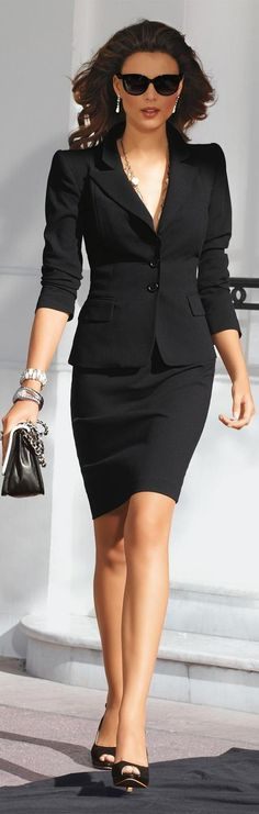 Classic black suit, black skirt, black pumps, and black purse, with gold and silver jewelry.