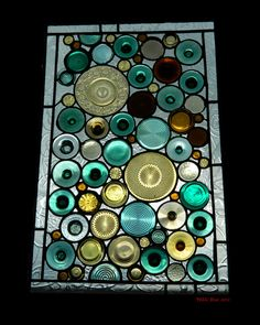Recycled stained glass window using glass plates, bottles, and wine glass bottoms.