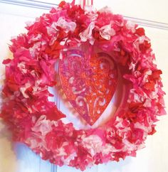 "My Valentine's Day Wreath - Styrofoam wreath base, tissue paper in red/pink/solids/prints cut with scalloping shears into 3 1/2"" squares punched and glued into base, center dangle is a romantic scalloped wood heart that I painted a pinkish red and covered with red glitter--until I ran out of red glitter at which point I used purple glitter  - a happy accident since I like the way it turned out! :D"