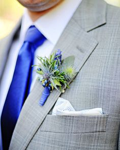 A boutonniere of thistle, blue privet berry, and blue muscari
