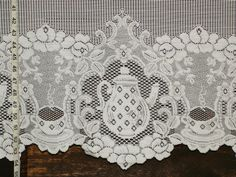 A teapot or tea pot lace fabric, with tea cups ! This is cafe lace, with holes for hanging at the top.