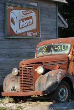 Old rusty truck for sale and old Holsum bread metal sign. Elwood, Indiana