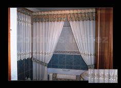 Cortinas en cuarto de baño, la ventana con visillo bordado y se le ha cosido una greca que sirve de cabecilla y montada en un conjunto de latón, cortina bañera de visillo bordado con volante y recogida con abrazaderas; Alfombra de baño confeccionada a juego con las cortinas