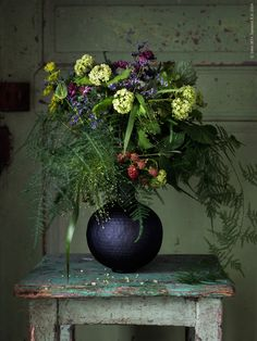 Express your flair for the dramatic with an arrangement of lush greenery and deep purple and red blooms in a dark vase, like ANGENÄM.