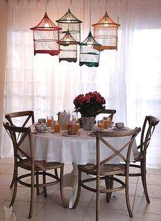 Criatividade! As gaiolas são transformadas em luminárias e dão um toque de humor para a sala de jantar