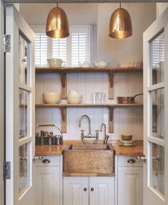 Copper sink with white cabinets, butcher block countertops.