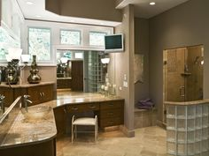 This contemporary bath incorporated glass blocks to enclose both the shower area and the water closet area. The curves softened the look of the square doors with stepped panels. The appliance garages below the corner windows gave additional countertop storage. -Gail Drury