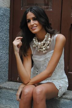 White lace dress & layered pearls .