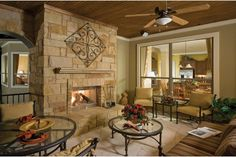 A rustic stone fireplace is the focal point in this covered patio. The Lundy model by David Weekley Homes at Meridian Estate Homes in Austin, TX.
