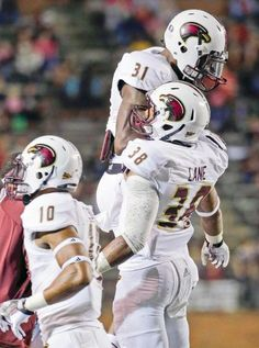 Louisiana-Monroe safety Mitch Lane (38) reacts with teammate Lenzy Pipkins (31) after Lane recovered a Troy fumble. At left is Louisiana-Monroe safety Cordero Smith (10). (Dave Martin/AP)