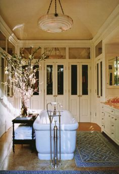 This room is a bathroom/dressing room. Look at the French doors and antiqued mirror transom detail above the doors.The room is punctuated by an alabaster pendant light and warm accents from the brass hardware to the coral marble. Also look at the fretwork/Greek key border on the rugs.