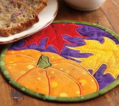 Autumn Leaves Mug Mat from Quilting Celebrations Fall 2013 is a mug mat quilt pattern featuring appliquéd fall leaves and a pumpkin.