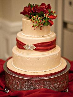 Pale Gold shimmering cake with Claret Roses and Hypericum Berries and and Claret Sash and Broach to match the Brides hair.  Beautiful Holiday season Wedding Cake.