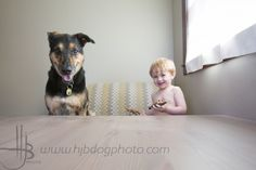 boy and his dog sitting at the table playing with dinosaurs