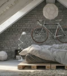 unmade pallet bed, grey exposed brick wall with mounted racing bike