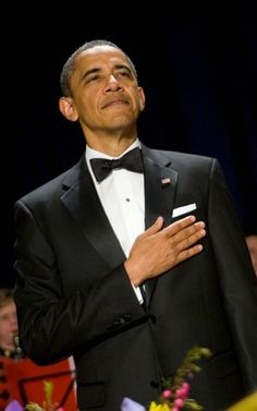 President Obama dressed appropriately in a black tuxedo with covered buttons and a black bow tie and accessorized with an American flag pin. Well done, Chief!