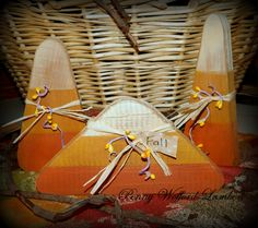 """Wooden Candy Corn.....  Painted, distressed  lightly stained for an aged, worn look. Tied with raffia  pip berries and a hang tag that says """"Fall"""". Blocks could slightly vary.  sizes approx.  Tallest 7""""x 3""""  Middle 6""""x 3.5""""  Shortest 4""""x 8"""""""