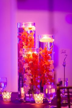 Rent cylinder vases and submerge orchids and top with floating candles for wedding centerpiece