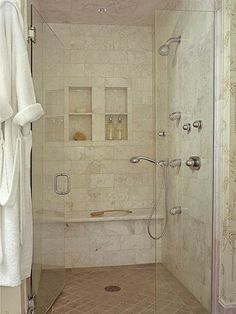 The shower's clear-glass doors show off walls covered in marble tiles. The rich pearl color and natural pattern variations of the tiles add interest. Two window-shape niches serve as functional storage for shower necessities, while two showerheads, multiple body sprays, and a bench foster modern pampering within the classic confines.