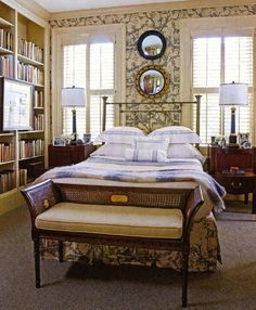 Bedroom by Gerald Pomeroy  in a historic Boston townhouse - plantation shutters, antique rattan backed bench, books