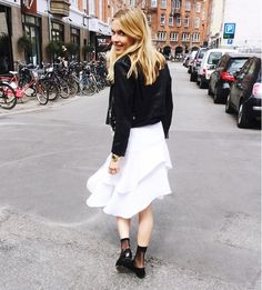 Pernille Teisbaek combines an edgy black leather jacket with a soft white skirt and black sheer socks for the ultimate day-to-night look. // #Fashion