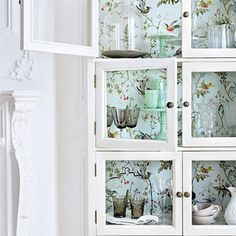 Love the white, glass cabinets with the floral wallpaper