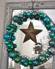 Love this bauble wreath!   It looks like a wire coat hanger - reshaped into a circle - and a slinky...then fill with Christmas baubles :) then hang a star from the center. Cute!