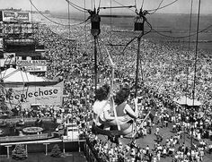 Two passengers on the parachute ride see throngs of people on the boardwalk and beach at the Coney Island Amusement Park in Brooklyn, New York, July 1, 1957. The Atlantic Ocean is also visible as they ride to the top of the tower. (AP Photo/AK)