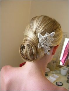 Chignon Bun Updo:    Hair is gorgeously tucked into a chignon bun and decked with a big hair accessory.