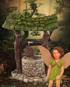 A little fairy makes a wish in a little wishing well in the fairy garden.