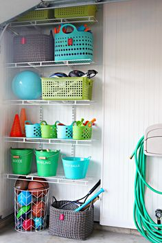 Garage organization for outdoor toys. Portable bins can be taken down to play and returned when finished. Step stool for kids to reach higher bins.