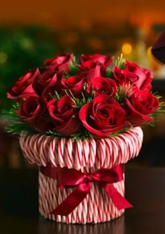 Stretch a rubber band around a cylindrical vase, then stick in candy canes until you cant see the vase. Tie a silky red ribbon to hide the rubber band. Fill with red and white roses or carnations. Good hostess gift for holiday parties. holiday parties, christmas centerpieces, white roses, rubber bands, candi cane, candy canes, hostess gifts, cylindr vase, silki red