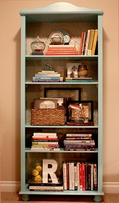 Bookcase Styled: wicker basket with things in it, the two horizontal stacks of books side by side.