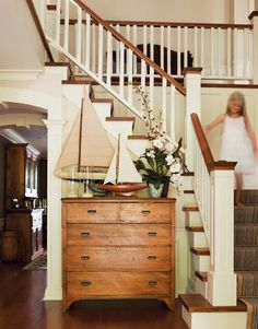 entry and hall showing different color wood tones in floor, stairs, railing, furniture, kitchen....