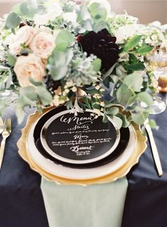 Hand calligraphed black menu card on silver, black, and white layered plates on a gold scalloped charger.  Dusty shale / mint napkin, black table linen, gold flatware.