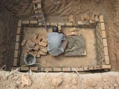 5. The builder begins by building up a rectangular brick structure within the pit, slightly away from the pit walls.