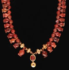 Egypt - NEW KINGDOM GOLD AND CARNELIAN NECKLACE   dynasty xviii-xix, 1550-1196 b.c.   Composed of twenty-eight flat carnelian lotus-seed pendants interspersed with globular and lozenge-shaped carnelian beads, and hollow, incised gold beads with cylindrical collars, the necklace centered by a Roman Period gold-mounted carnelian scarab pendant with a gold lentoid suspension, set with a small cabachon garnet
