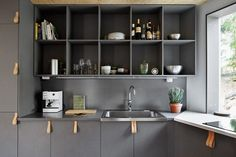 Swedish lake house by architect Tommy Carlsson, gray kitchen cabinets with leather cabinet handles, photographed by Andy Liffner