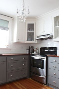 LOVE THIS!  White top cabinets, white subway tile backsplash, grey bottom cabinets, walnut counter tops, walnut laminate flooring or stained concrete.